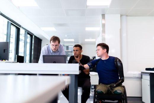 Disabled man pointing at a computer with coworkers