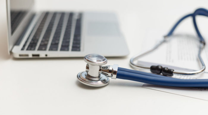 Stethoscope and laptop on doctor working desk, business and health care concept.