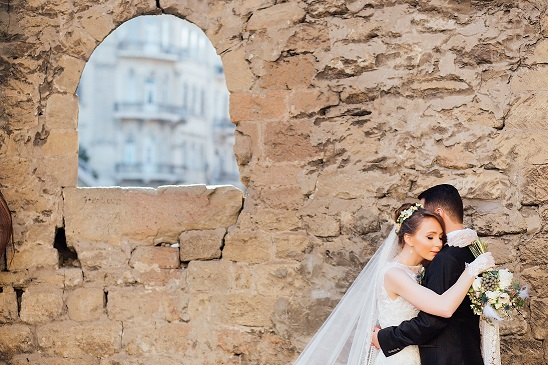 married couple embracing in front of a stone wall - Karlin Law