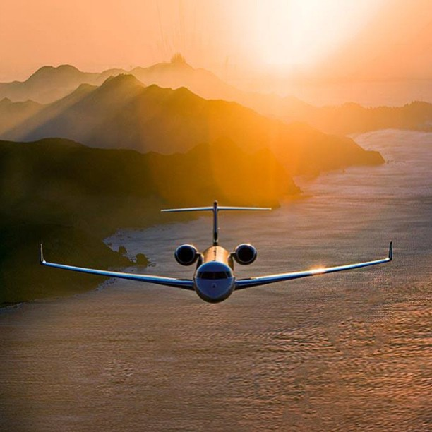 private jet flying at sunset